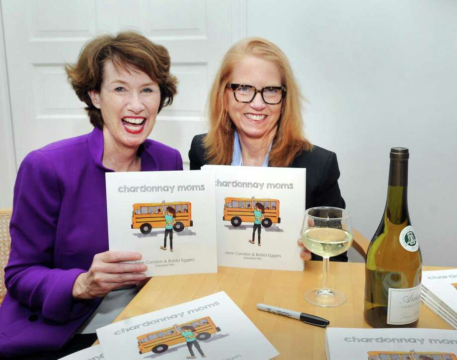 "Jane Condon, left, and Bobbie Eggers, with their recently published book, ""Chardonnay Moms,"" featuring their greatest hits cartoons poking fun at the lighter side of Greenwich at Condon's home in Greenwich on Thursday. Photo: Bob Luckey Jr. / Hearst Connecticut Media / Greenwich Time"