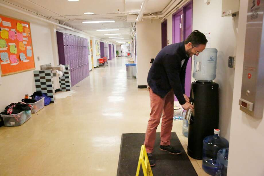 Ryan Chapman, head of school at the New School in S.F., fills up at a water dispenser as a fountain remains covered (left). Photo: Lea Suzuki, The Chronicle