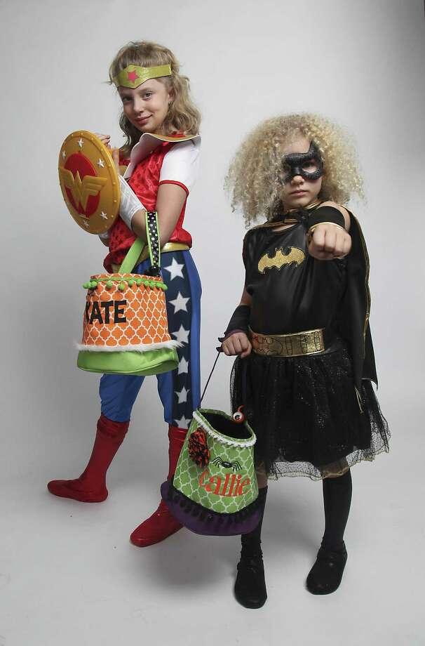 Sisters Kate Hoopingarner, 10, Wonder woman, Callie Hoopingarner, age 5, Batgirl. Photo: Juanito M. Garza /San Antonio Express-News / San Antonio Express-News