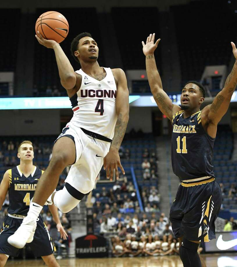 UConn's Jalen Adams, left, shoots over Merrimack's Tawayne Anderson during the first half of Monday's exhibition game in Hartford. Photo: Jessica Hill / Associated Press / AP2017
