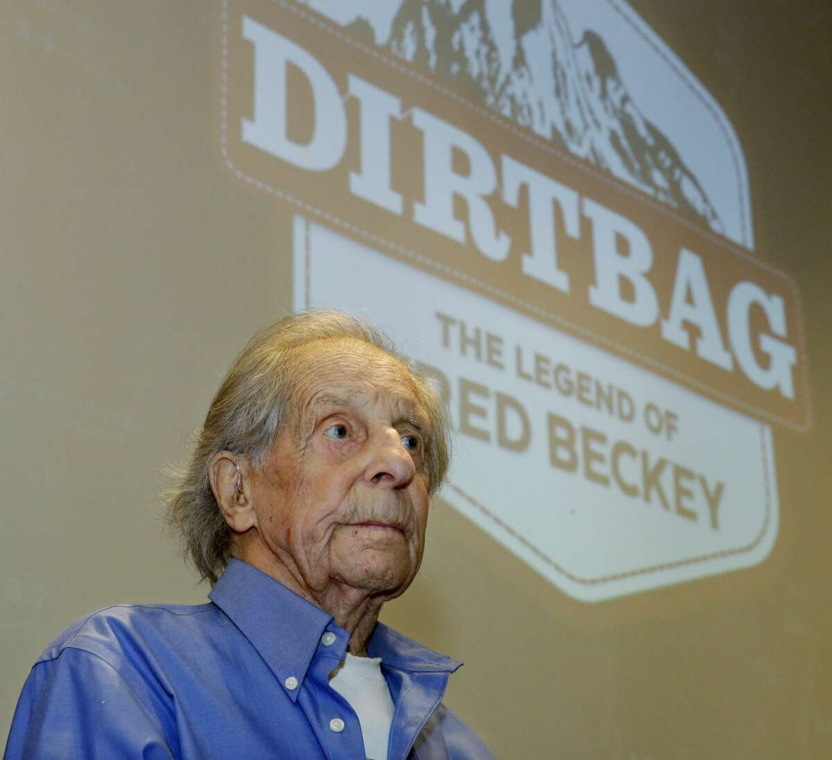 In this photo taken July 26, 2016 in Seattle, Fred Beckey, the legendary mountain climber who has bagged more first ascents than any other mountaineer and wrote the definitive guidebooks to a major North American mountain range, sits in front of a screen bearing the logo for