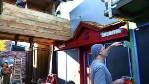 Friend of Jon Chambers, Lukas Velush paints a storefront as his daughter, Tansy, watches from a walkway above as the finishing touches are put on a re-creation of Diagon Alley, a shopping street location from the Harry Potter books, before it opens on Halloween, Monday, Oct. 30, 2017. Jon Chambers, who just left a job in the tech industry, has spent the past two weeks building the the set in his driveway in Ballard with the help of friends. They have created many of the fictional storefronts including Eeylops Owl Emporium, Ollivanders Wand Shop, Madam Malkin's Robes for All Occasions, Quality Quidditch Supplies, Flourish and Blotts book shop, Magical Menagerie, and may add Gringotts Wizarding Bank, time permitting.  Chambers' creation will be open for the next few weeks (possibly until Christmas), and his daughters will be collecting donations to support pancreatic cancer research.