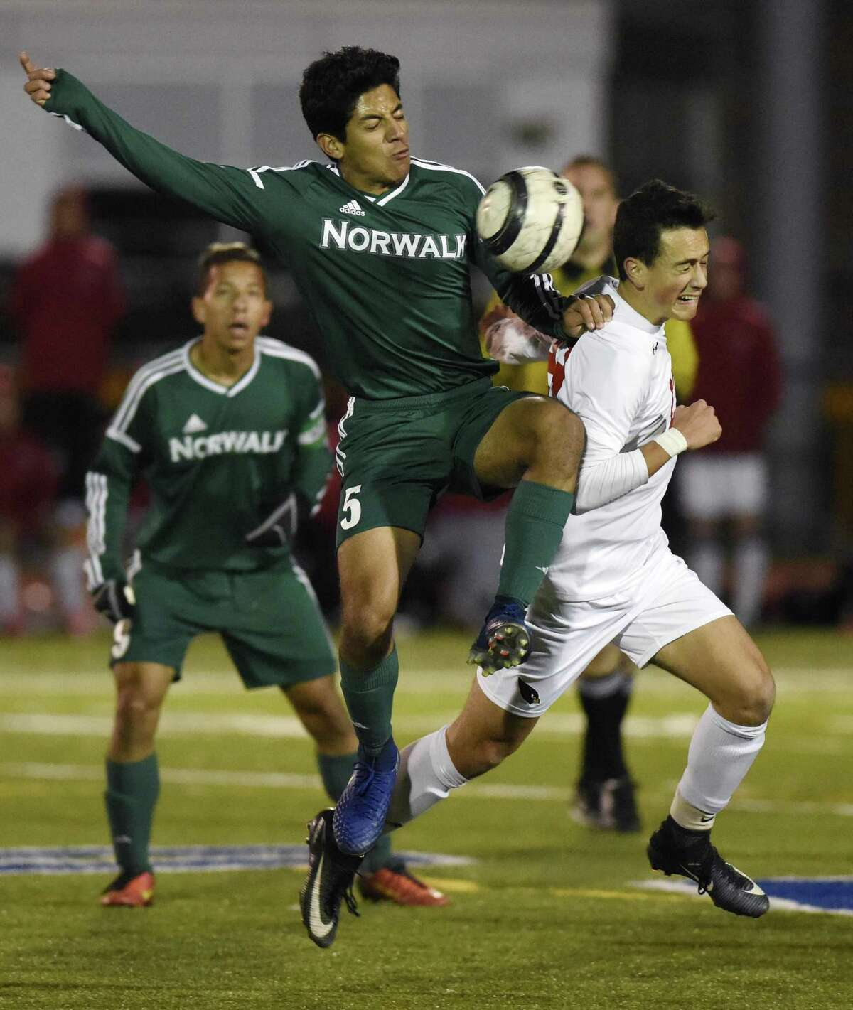 Norwalk's Fredy Rosales, left, and Greenwich's Martin Garcia jump for the ball in Monday's FCIAC semifinal at Fairfield Ludlowe High School on Monday.