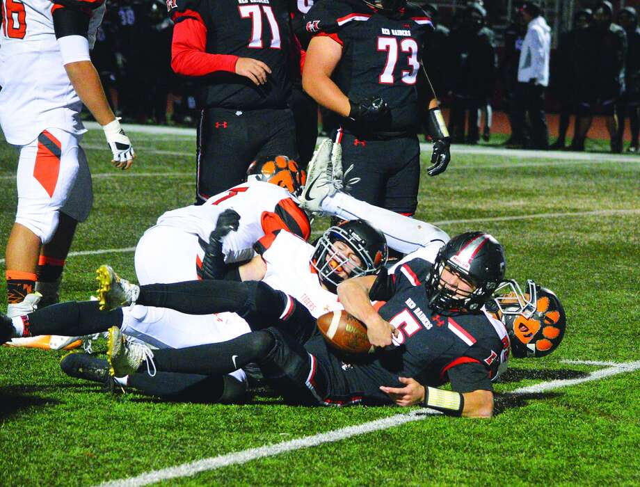 The Edwardsville defense tackles Huntley quarterback Eric Mooney during first-half action in the opener of the Class 8A postseason.