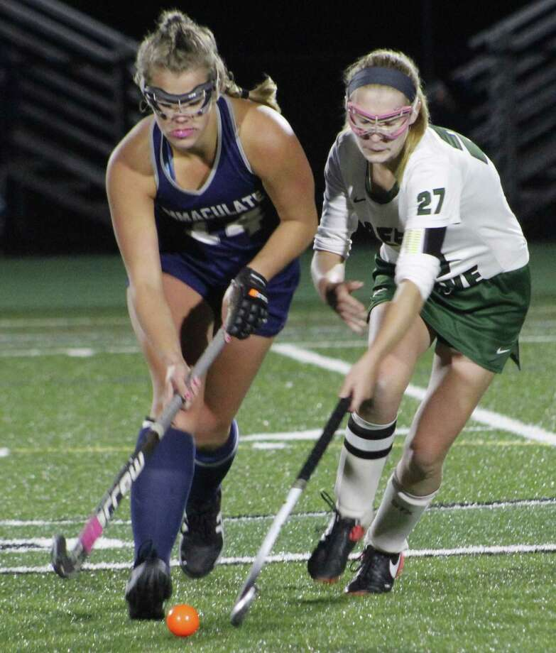 Immaculate's Madison Halas, left, looks to make a play as New Milford's Kelli Souza defends during the SWC semifinal field hockey game at New Milford High School Oct. 30, 2017. Photo: Richard Gregory / Richard Gregory