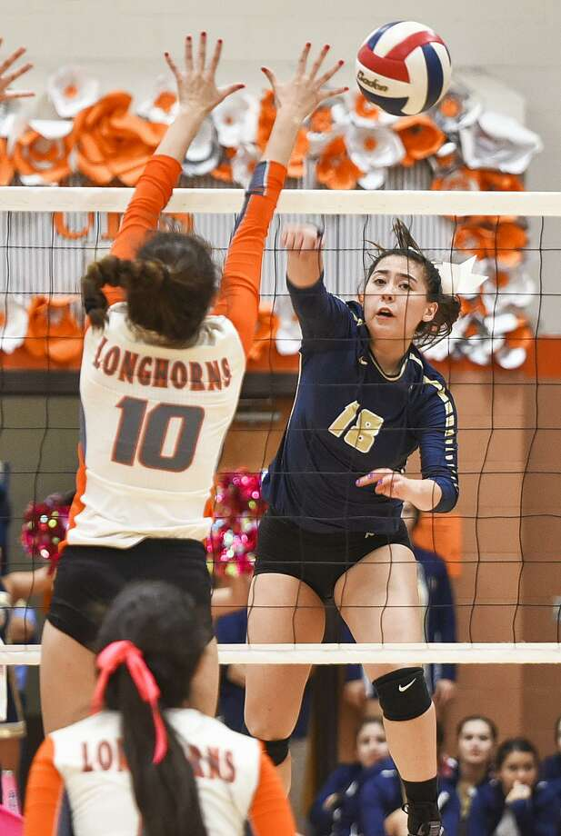 Alexander High School Amber Tran attacks as United High School Carolina Medellin reaches for the block on Oct. 24, 2017, during a game at United High School. Photo: Danny Zaragoza /Laredo Morning Times File / Laredo Morning Times