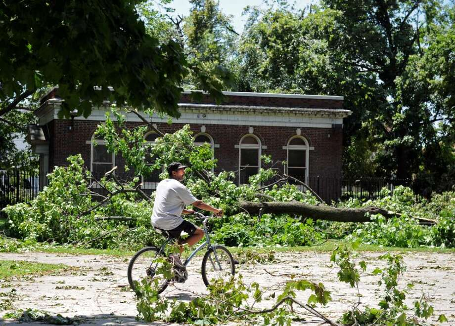 Tony Williamson, of Bridgeport, rides his bike past downed trees at Washington Park in Bridgeport Friday June 25, 2010.  The damage was the result of a tornado with 100 mph winds that touched down in Bridgeport Thursday. Photo: Autumn Driscoll / Connecticut Post