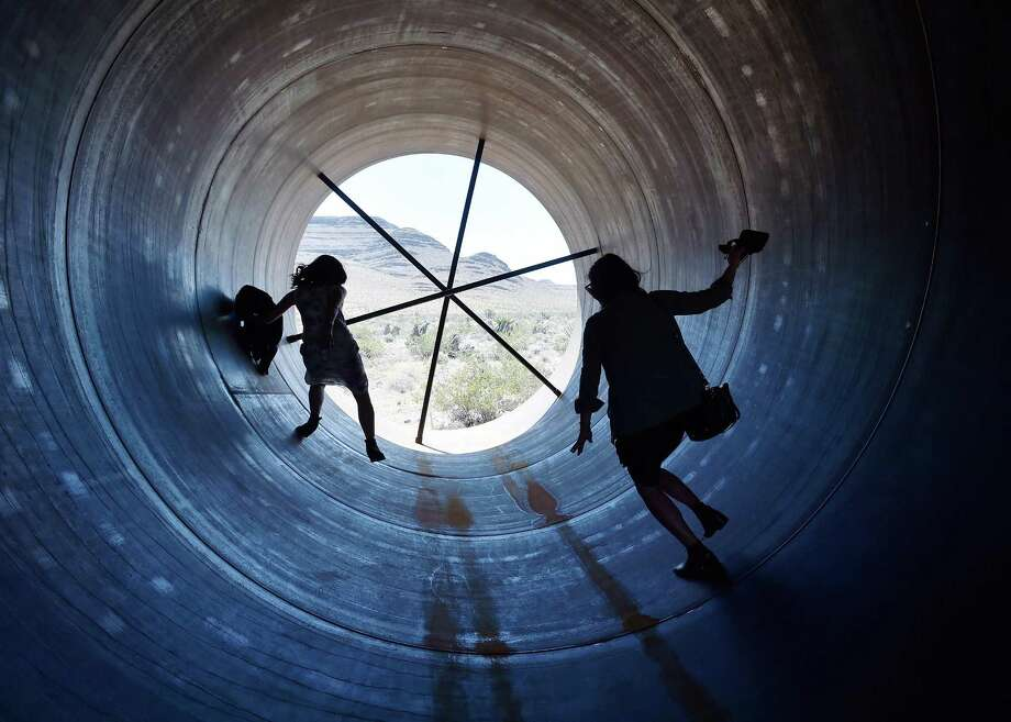 People walk through a Hyperloop tube. Elon Musk has been given approval to start digging 10 miles of tunnels under the Baltimore-Washington Parkway that will whisk people along at more than 700 mph. Photo: David Becker / Getty Images / 2016 Getty Images