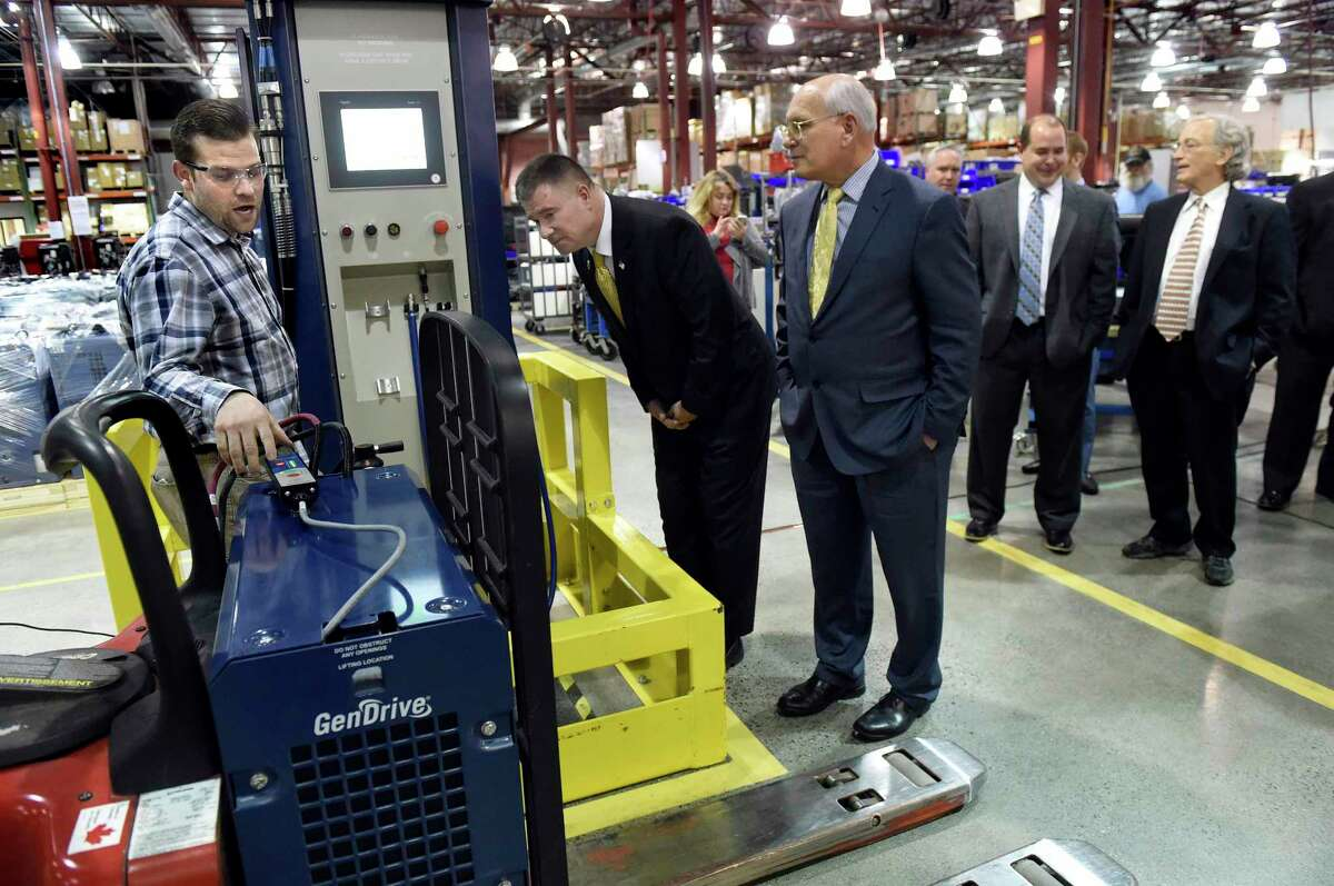 Quality control Aaron Currado, left, fuels up a pallet jack at a refueling station as Rep. Chris Gibson, center, and Rep. Paul Tonko tour the plant on Tuesday, Feb. 16, 2016, at Plug Power in Latham, N.Y. (Cindy Schultz / Times Union)
