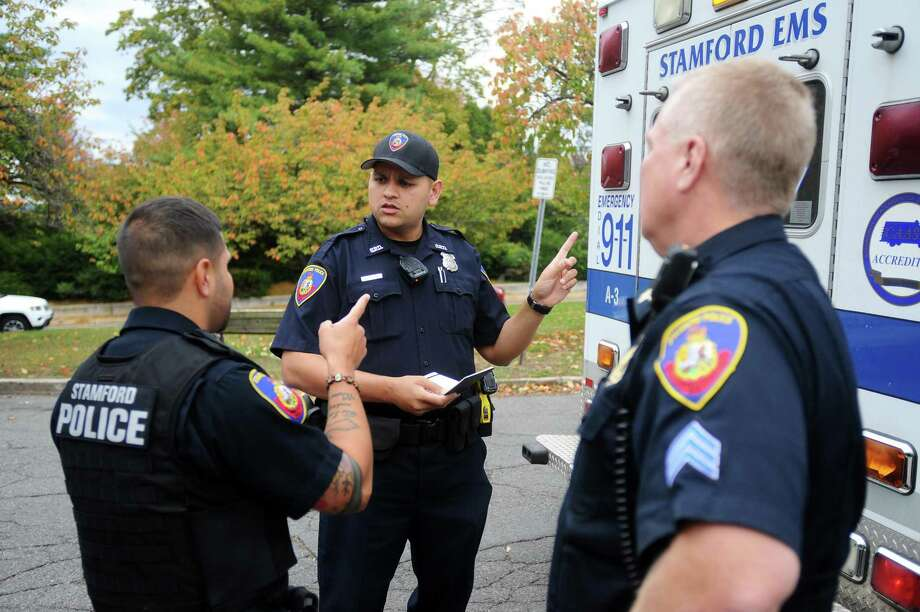 "Recruit Abhishek Herekar, center, has a discussion about proper protocol with Field Training Officer William Garay, left, and Sgt. Charles ""Chip"" White after responding to a call on Cove Road in Stamford, Conn. on Thursday, Oct. 26, 2017. Photo: Michael Cummo / Hearst Connecticut Media / Stamford Advocate"