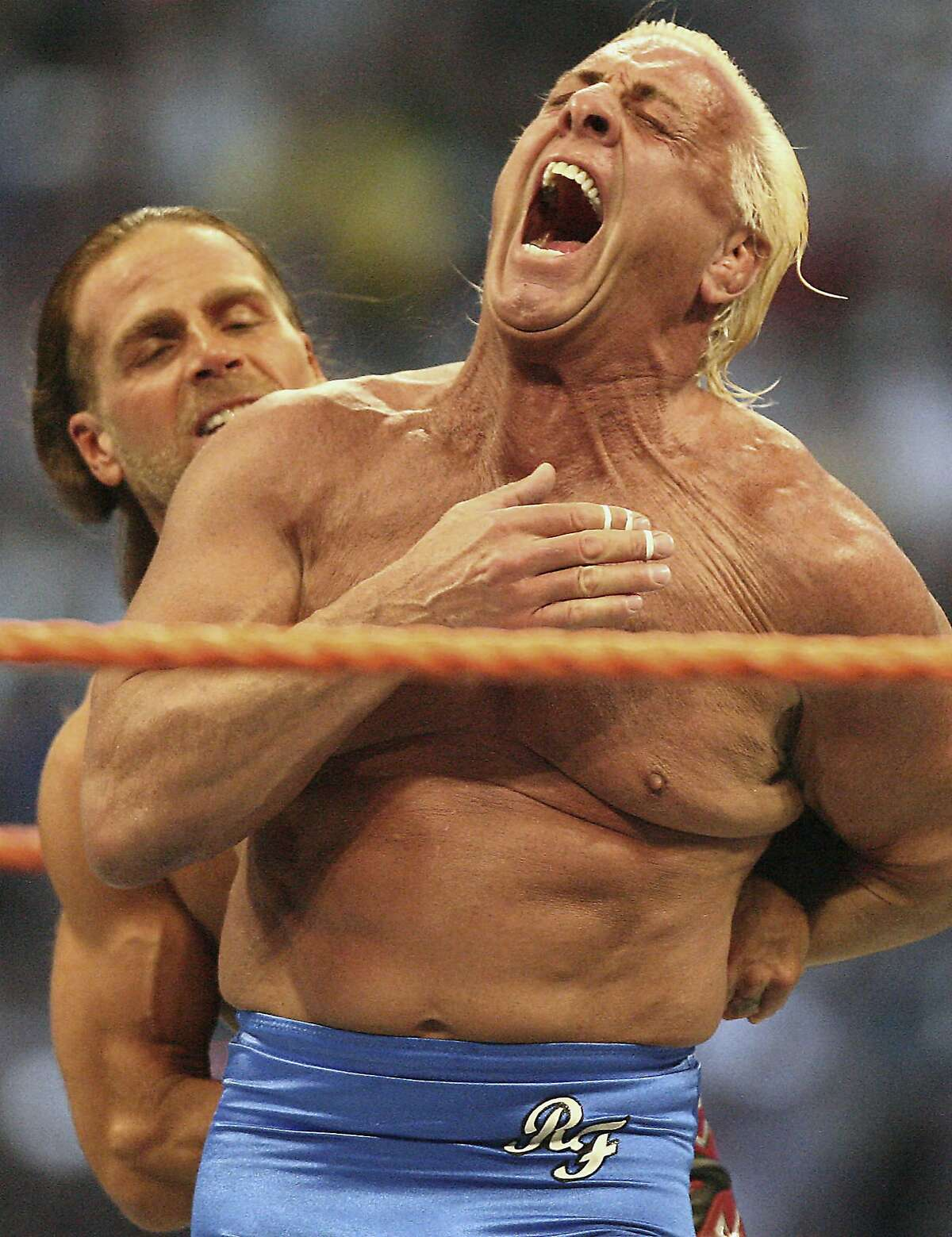 FILE - In this March 30, 2008, file photo, Ric Flair right, reacts as Shawn Michaels puts him in a hold during the Career Threatening Match at WrestleMania XXIV at the Citrus Bowl in Orlando, Fla. Flair, whose