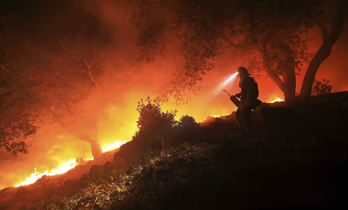 FILE - In this Wednesday, Oct. 11, 2017 file photo, a San Diego Cal Fire firefighter monitors a flare up on a the head of a wildfire (the Southern LNU Complex), off of High Road above the Sonoma Valley, in Sonoma, Calif. Top U.S. House Democrat Nancy Pelosi and five other members of Congress plan to tour wildfire-ravaged Northern California on Saturday, Oct. 28, 2017, as families and communities begin the long process of rebuilding. Pelosi, of San Francisco, will spend a day touring the fire zones and meeting with officials and victims. (Kent Porter/The Press Democrat via AP, File)