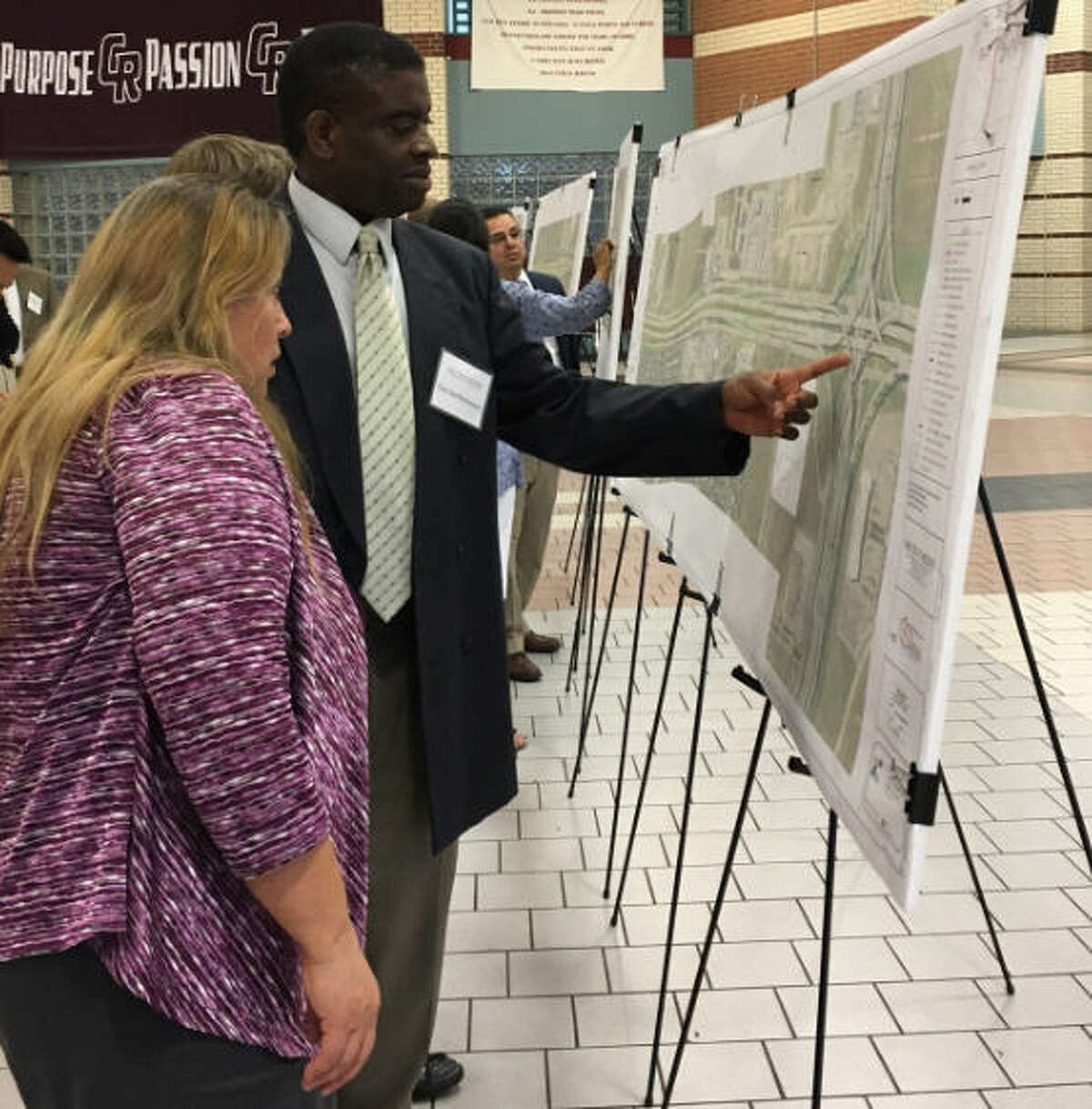 Paul Bartholomew of the Texas Department of Transportation talks about the proposed widening of Texas 99 with one of the residents who visited the department's open house meeting Oct. 24 at Cinco Ranch High School.