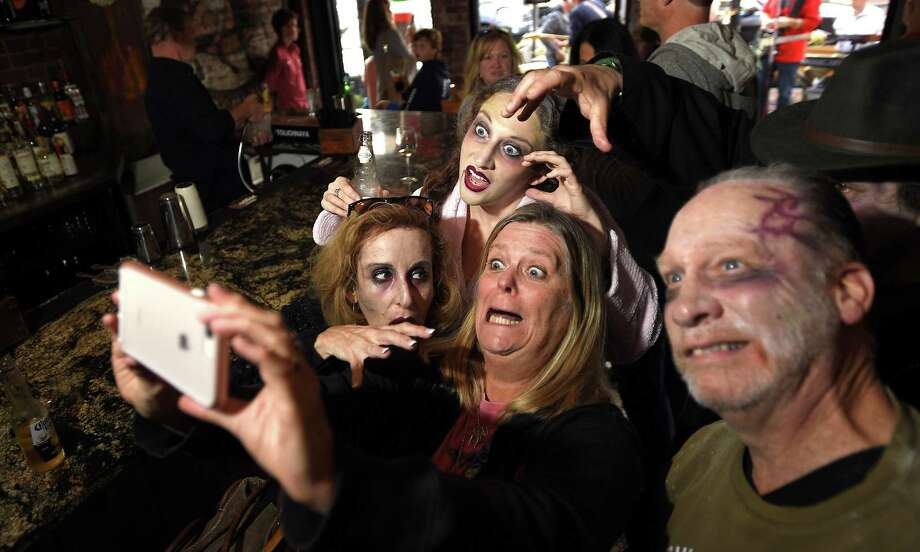 Brent McKinley, center, takes a selfie with some of her zombie friends, from left, Merryl Hackman, Meredith Hackmand and Anthony Briskin, during the first Springdale zombie bar crawl on Saturday. The event raised funds to support Healing Hearts, a program at Break Thru Family Fitness. Healing Hearts Recreational and Social Division is dedicated to improving the lives of children, teens and adults with a range of developmental disabilities and neuro-motor challenges. Photo: Matthew Brown / Hearst Connecticut Media / Stamford Advocate