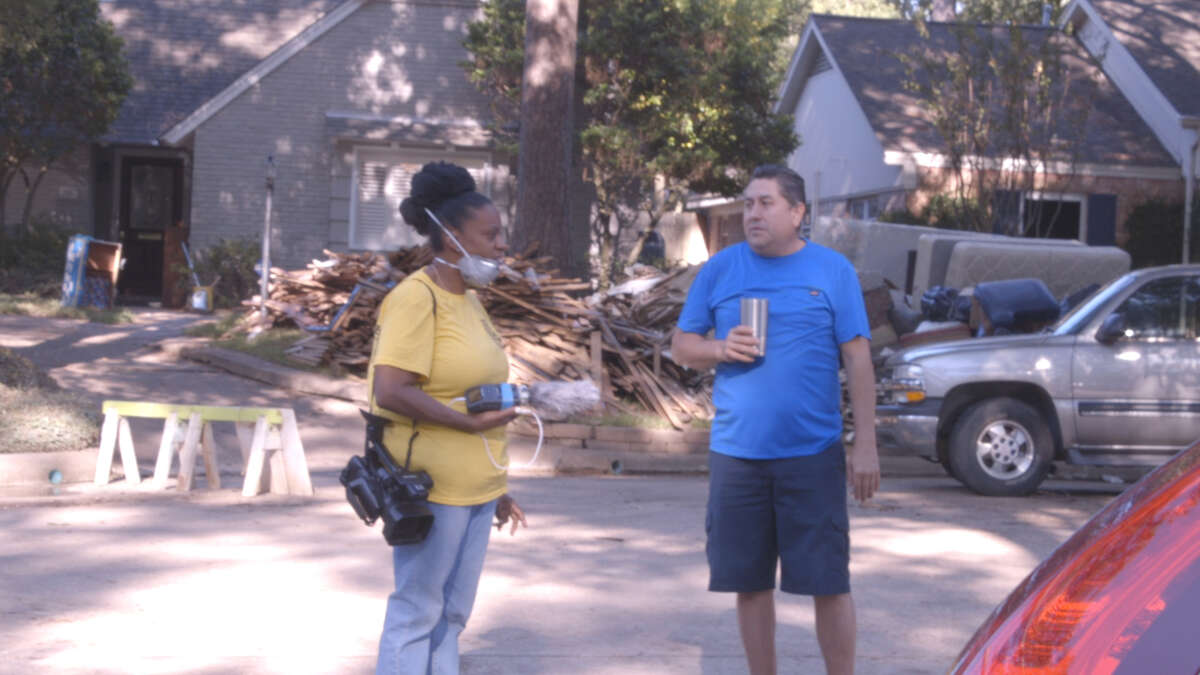 Lisa Alexander interviews Jose Angel Serrano Lopez as he helps move the belongings of afamily whose home flooded. Alexander and her husband Elgin, shot and interviewed Mercy Response volunteers who helped homeowners gut and clean out their homes after Hurricane Harvey.