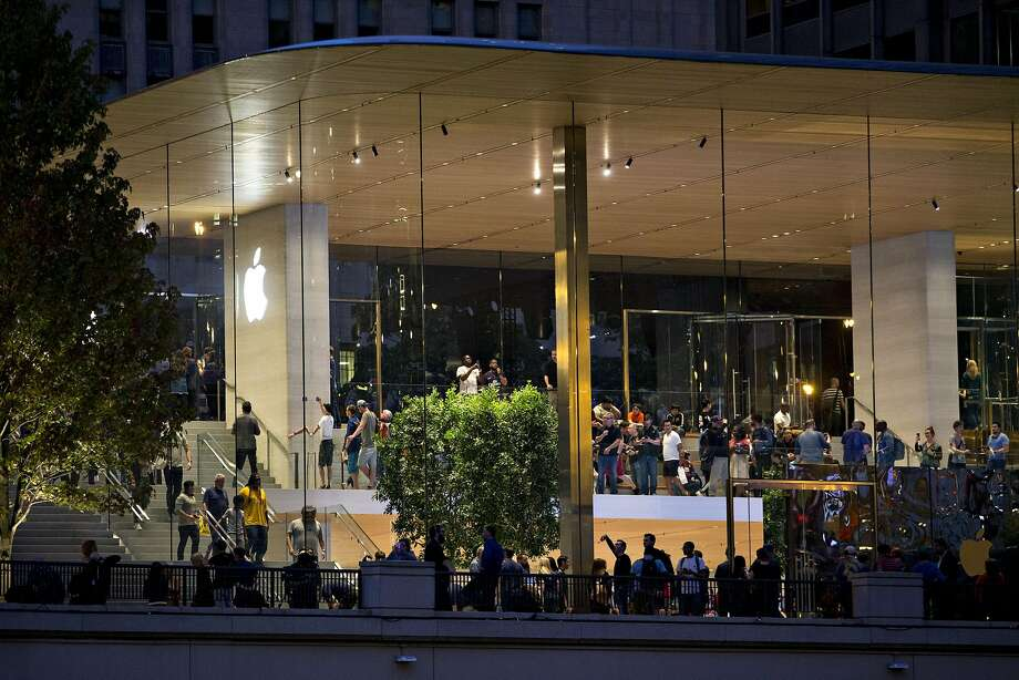 Customers are seen during the opening of the new Apple Inc. Michigan Avenue store in Chicago on Friday, Oct. 20, 2017. The building features exterior walls made entirely of glass with four interior columns supporting a 111-by-98 foot carbon-fiber roof, designed to minimize the boundary between the city and the Chicago River. Photo: Daniel Acker, Bloomberg