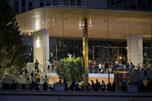 customers are seen during the opening of the new Apple Inc. Michigan Avenue store in Chicago, Illinois, U.S., on Friday, Oct. 20, 2017. The building features exterior walls made entirely of glass with four interior columns supporting a 111-by-98 foot carbon-fiber roof, designed to minimize the boundary between the city and the Chicago River. Photographer: Daniel Acker/Bloomberg