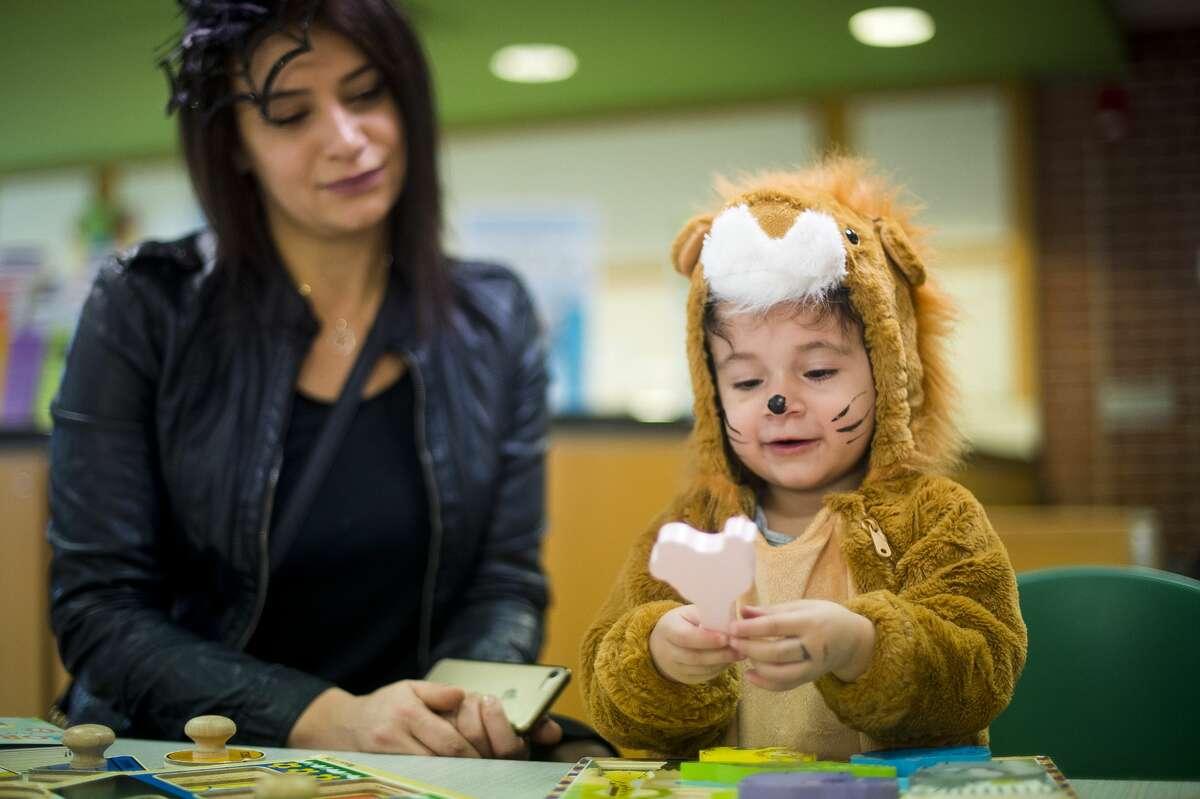 Heidi Makki, 2, puts together a puzzle alongside Maya El Hajj during a Halloween party on Tuesday, Oct. 31, 2017 at Grace A. Dow Memorial Library. (Katy Kildee/kkildee@mdn.net)