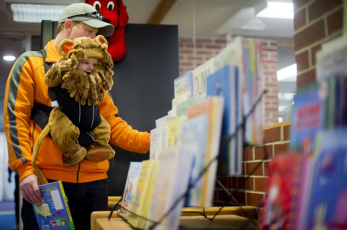 Kevin Caldwell of Sanford checks out a book while his son, Cohen Caldwell, 4 months, hangs out in his lion costume during a Halloween party on Tuesday, Oct. 31, 2017 at Grace A. Dow Memorial Library. (Katy Kildee/kkildee@mdn.net)