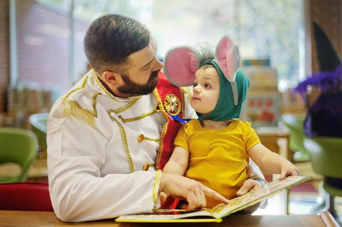 Nick Saum of Midland, dressed as Prince Charming from Cinderella, checks out a book with his son, Heath Saum, 15 months, dressed as Gus the mouse from Cinderella, during a Halloween party on Tuesday, Oct. 31, 2017 at Grace A. Dow Memorial Library. (Katy Kildee/kkildee@mdn.net)