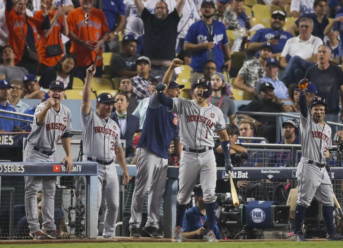 The Astros dugout reacts to Houston Astros center fielder George Springer's eleventh inning two-run home run in Game 2 of the World Series at Dodger Stadium on Wednesday, Oct. 25, 2017, in Los Angeles.