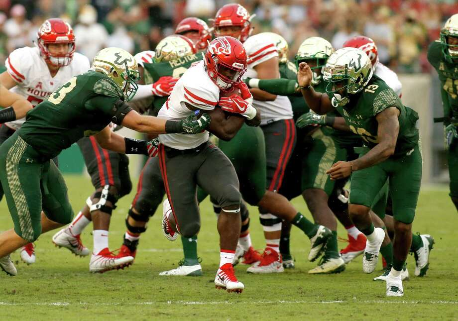 TAMPA, FL - OCTOBER 28: Running back Mulbah Car #34 of the Houston Cougars runs for a first down between linebacker Auggie Sanchez #43 of the South Florida Bulls and safety Tajee Fullwood #13 during the third quarter of an NCAA football game on October 28, 2017 at Raymond James Stadium in Tampa, Florida. (Photo by Brian Blanco/Getty Images) Photo: Brian Blanco, Stringer / 2017 Getty Images