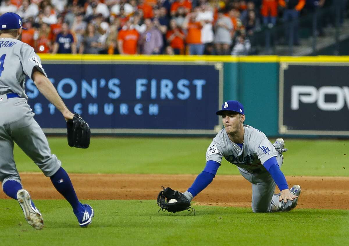 Los Angeles Dodgers first baseman Cody Bellinger (35) makes a diving catch of Houston Astros right fielder Josh Reddick (22) pop bunt during the seventh inning of Game 3 of the World Series at Minute Maid Park on Friday, Oct. 27, 2017, in Houston.