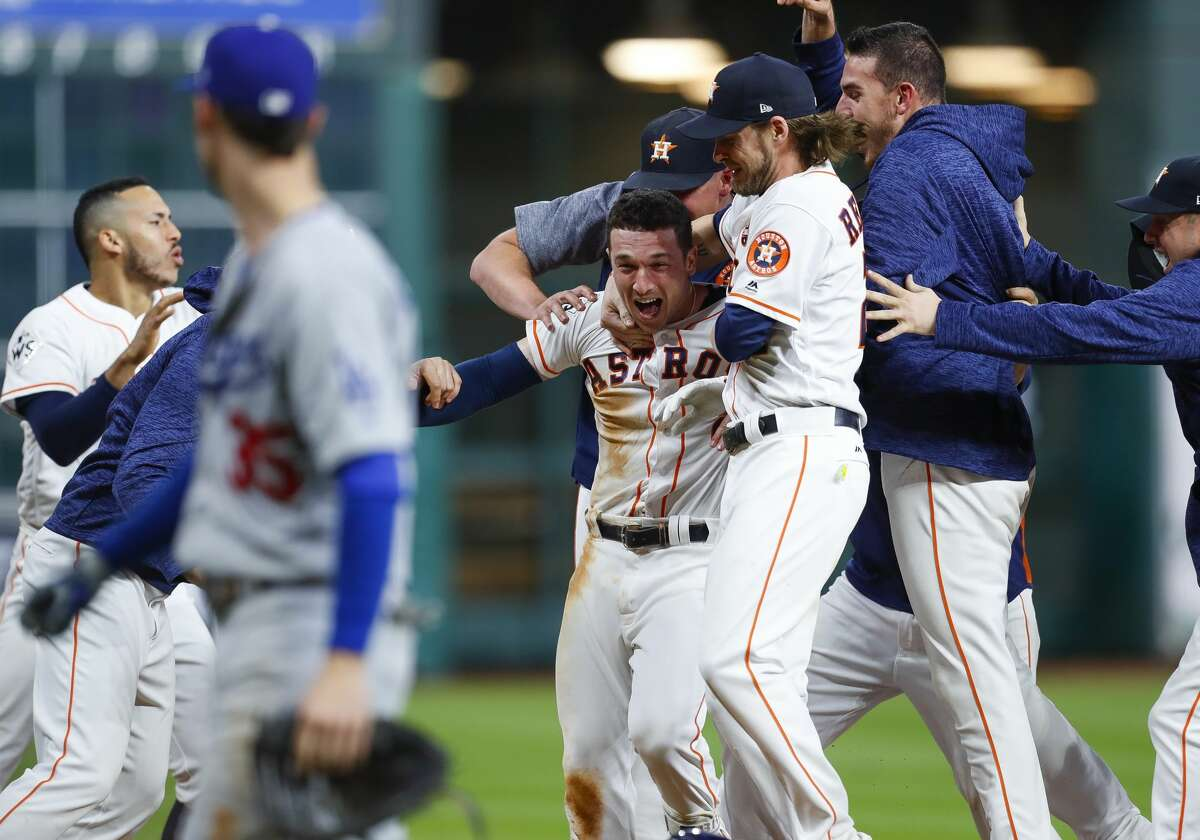 Houston Astros third baseman Alex Bregman (2) is surrounded by his teammates after hitting a walk off single that drove in left fielder Derek Fisher (21) to give the Astros a 13-12 victory over the Los Angeles Dodgers in the tenth inning of Game 5 of the World Series at Minute Maid Park on Monday, Oct. 30, 2017, in Houston.