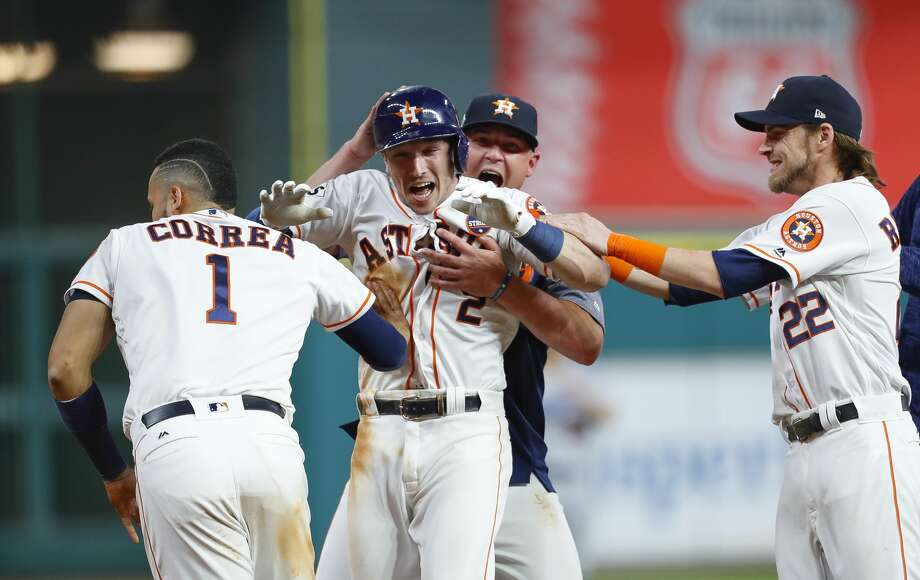Houston Astros third baseman Alex Bregman (2) is surrounded by his teammates after hitting a walk off single that drove in left fielder Derek Fisher (21) to give the Astros a 13-12 victory over the Los Angeles Dodgers in the tenth inning of Game 5 of the World Series at Minute Maid Park on Monday, Oct. 30, 2017, in Houston. Photo: Brett Coomer/Houston Chronicle