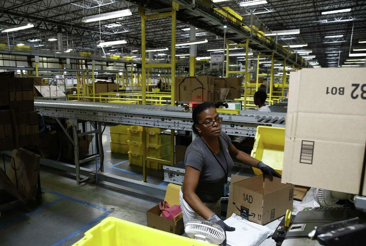 In this Aug. 3, 2017, photo, Myrtice Harris packages products for shipment at an Amazon fulfillment center in Baltimore. Some 94 percent of customers worldwide are shopping online, according to a new Pitney Bowes study.