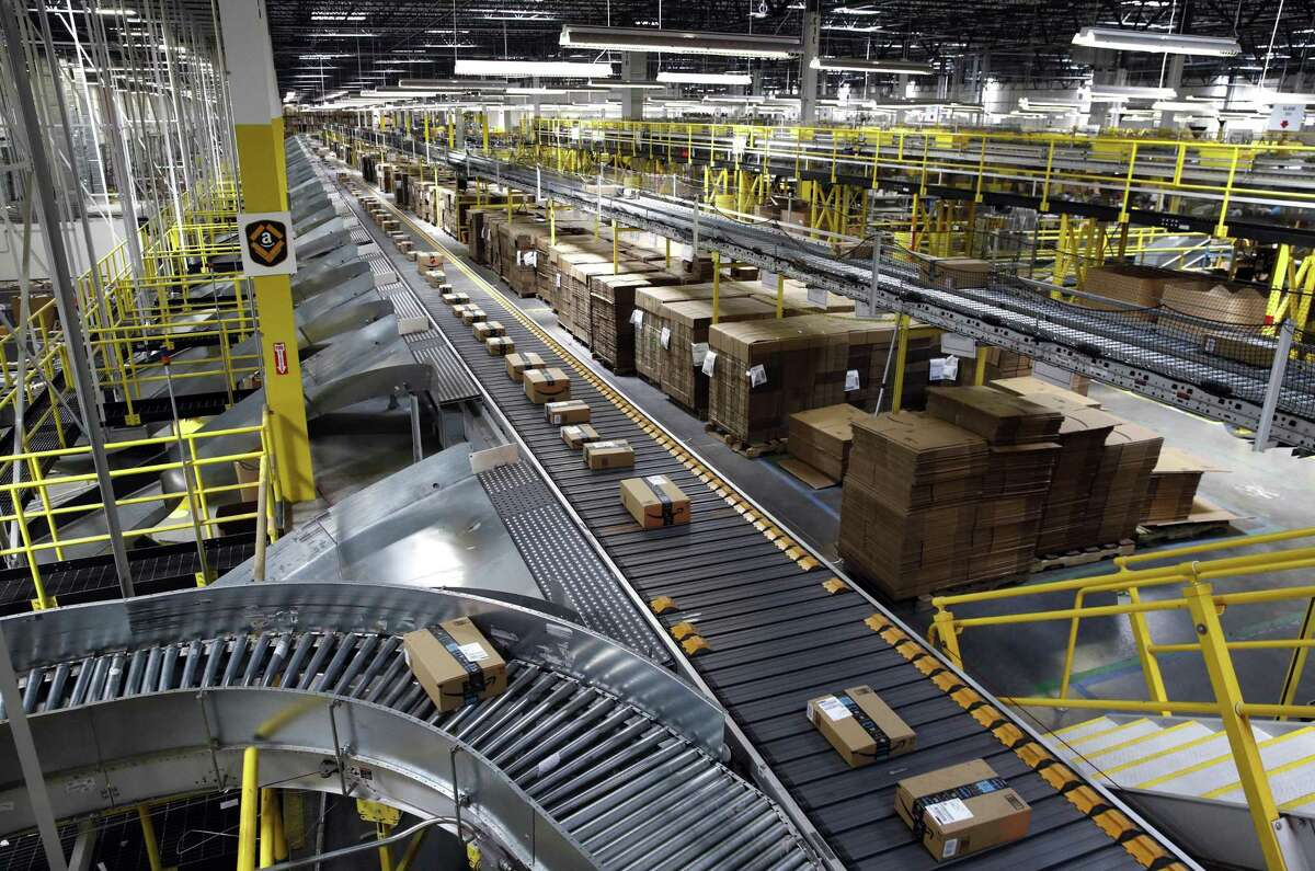 In this Aug. 3, 2017, photo, packages ride on a conveyor system at an Amazon fulfillment center in Baltimore. Some 94 percent of customers worldwide are shopping online, according to a new Pitney Bowes study.