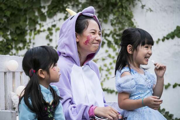 Children wearing costumes participate in the parade on Halloween day.
