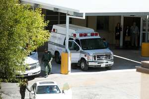 In this Wednesday, Oct. 25, 2017 photo, a United States Customs and Border Protection agent walks away after helping to place an undocumented 10-year-old girl with cerebral palsy in the back of an ambulance to transfer her from Driscoll Children's Hospital in Corpus Christi, Texas, to a children's facility in San Antonio for emergency gallbladder surgery.  Immigration advocates are protesting the case and say Border Patrol should show more discretion in the cases of sick children who are in the U.S. illegally but need medical treatment. (Courtney Sacco/Corpus Christi Caller-Times via AP)
