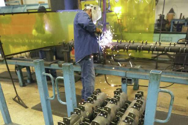 Welders work on equipment used in mowers at Alamo Group Manufacturing facility in August. Manufacturing in San Antonio is experiencing robust growth.