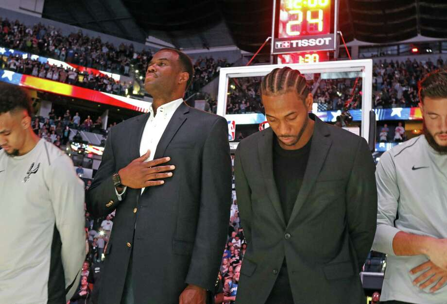 Former Spurs star David Robinson, left, joins injured Kawhi Leonard during the national anthem before the game against the Minnesota Timberwolves at AT&T Center on October 18. With sports wracked by so much controversy, including kneeling before the anthem, a readers says current players could look up to Robinson as a role model. Photo: Ronald Cortes /Getty Images / 2017 Getty Images