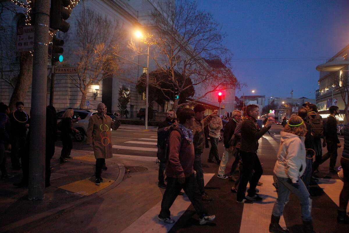 UnSilent Night participants crossing at Franklin and Grove Streets in San Francisco while playing the music as they go on December 19, 2015.