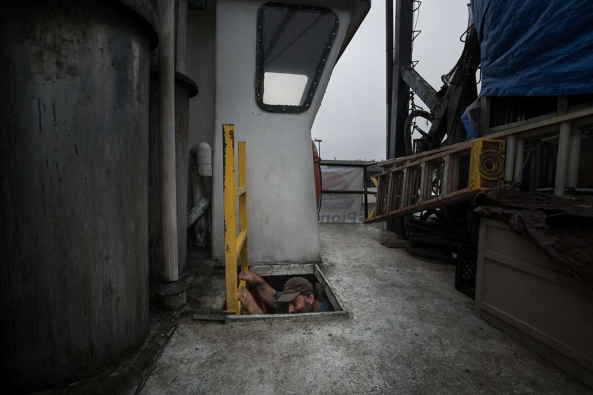 Joe Pennisi climbs down the upper deck of his fishing boat, The Pioneer, while docked on Pier 47 in San Francisco.