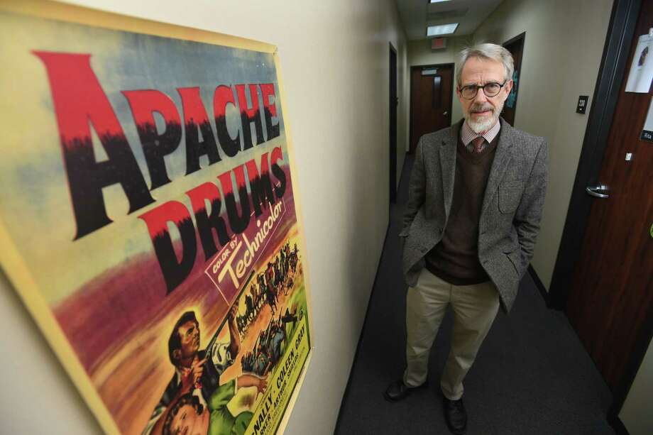 David Hooker with a painting of one of his movie posters. Hooker a Lamar Institute of Technology professor wrote a book about Beaumont and its movie history. Photo taken Wednesday, October 26, 2017 Guiseppe Barranco/The Enterprise Photo: Guiseppe Barranco, Photo Editor / Guiseppe Barranco ©