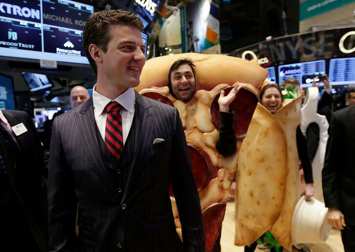 GrubHub Inc. CEO Matthew Maloney, trailed by costume characters, walks the New York Stock Exchange trading floor before his company's IPO begins trading, Friday, April 4, 2014. Investors sent shares of the online food ordering service up 51 percent to $39.20 in early trading in its stock market debut Friday. (AP Photo/Richard Drew)