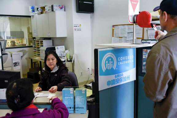 Representative Nancy Chen helps a customer with coverage at Asian Health Services in Oakland, Calif., as another customer takes a number.
