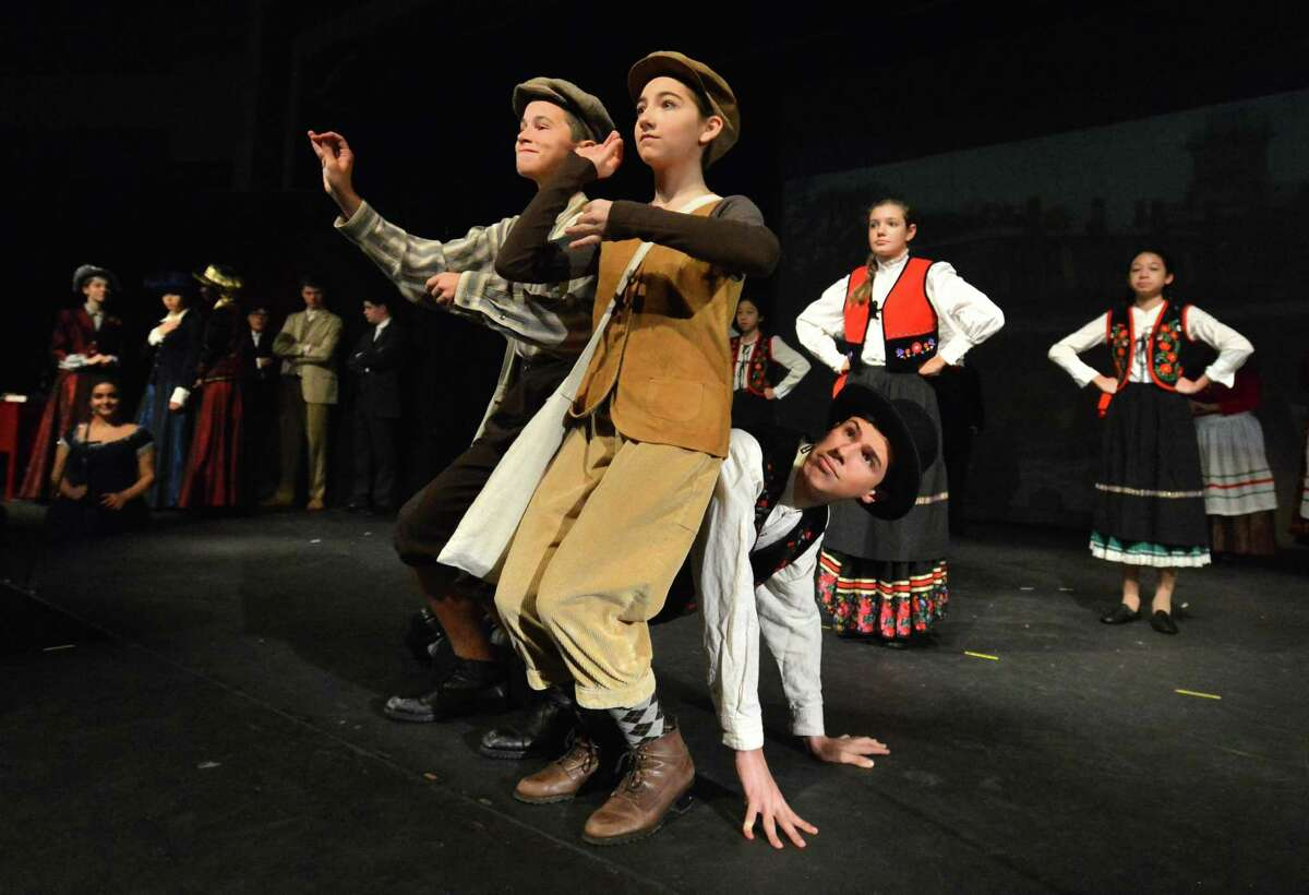 Paperboys Anthony Vayda and Ava Breisler try and stay calm while seated on Sam Facone's back during a scene from 'Whistleville' , on Sunday October 29, 2017 in Norwalk Conn. Whistleville is a historical musical about South Norwalk that is performed by theater students at The Crystal Theater and opens this Saturday.