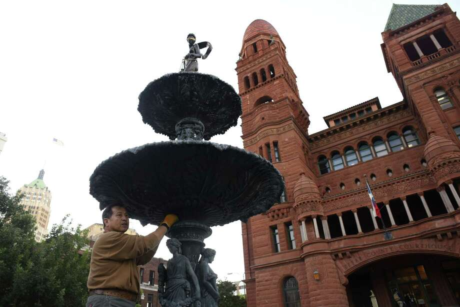 Gilbert E. Barrera uses steel wool on the 121-year-old fountain in front of the old Bexar County Courthouse, where he is touching up the refurbished fountain. He created the new statue of Lady Justice, which stands atop the fountain. Photo: Billy Calzada /San Antonio Express-News / San Antonio Express-News