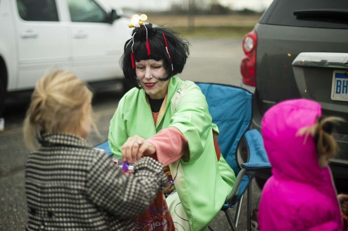 Tina Garrett of Midland passes out candy during Trunk-N-Treat at Messiah Lutheran Church on Tuesday, Oct. 31, 2017 in Midland. (Katy Kildee/kkildee@mdn.net)