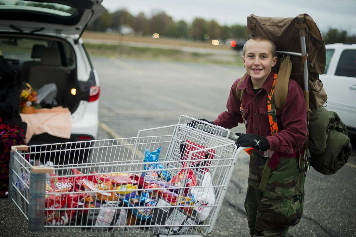 Calyb Wishowski, 11, dressed as a survivalist, replenishes candy supplies for those passing out candy during Trunk-N-Treat at Messiah Lutheran Church on Tuesday, Oct. 31, 2017 in Midland. (Katy Kildee/kkildee@mdn.net)