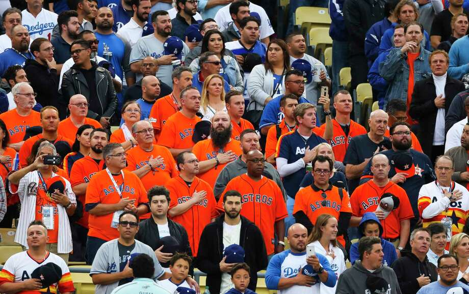 """PHOTOS: A look at Astros fans at Dodger Stadium for Game 6  Astros fans flown in by Jim """"Mattress Mack"""" McIngvale listen to the National Anthem before Game 6 of the World Series at Dodger Stadium on Tuesday, Oct. 31, 2017, in Los Angeles.  Browse through the photos for a look at Astros fans at Dodger Stadium for Game 6. Photo: Michael Ciaglo, Houston Chronicle / © 2017 Houston Chronicle"""