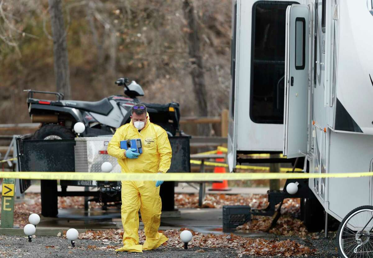 An investigator emerges with evidence from a trailer in a park along Clear Creek in which the body of a 63-year-old man was found Tuesday, Oct. 31, 2017, in Golden, Colo. Police say that a man arrested in a fatal carjacking near the University of Utah is wanted for questioning in the death of the man in Golden. (AP Photo/David Zalubowski)