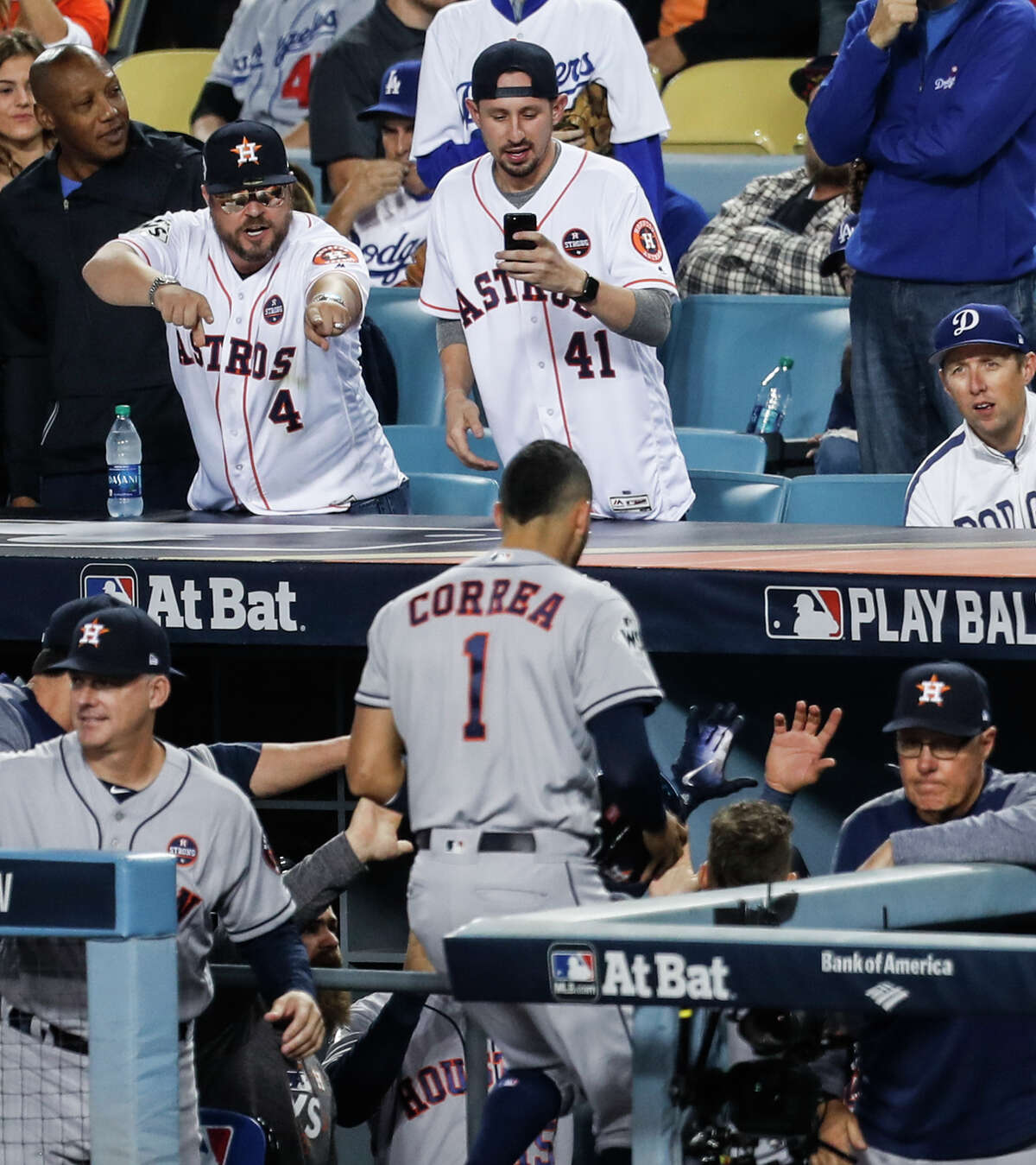 Houston Astros fans cheer after Houston Astros center fielder George Springer hit a solo home run off Los Angeles Dodgers starting pitcher Rich Hill during the third inning of Game 6 of the World Series at Dodger Stadium on Tuesday, Oct. 31, 2017, in Los Angeles.
