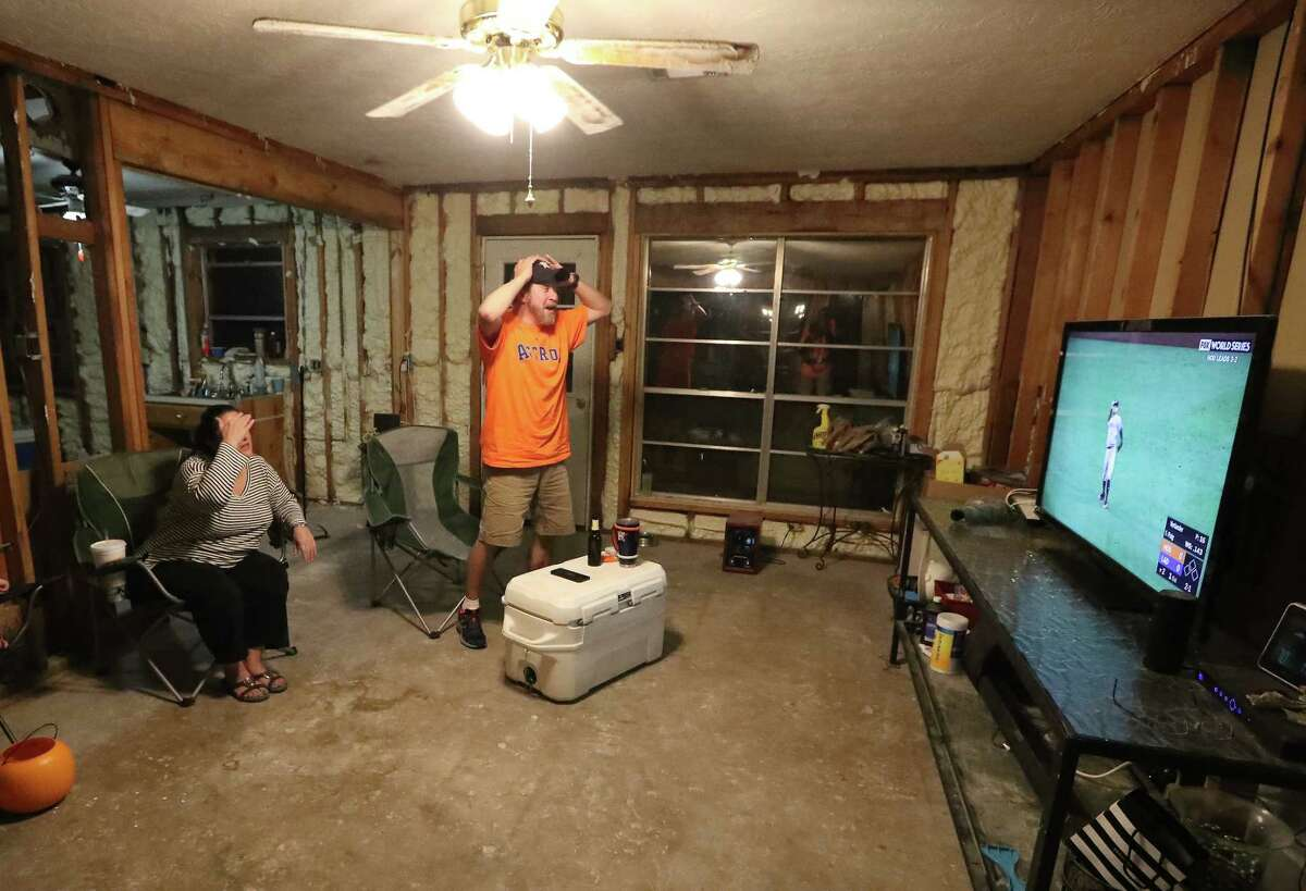 Astros fans Jim and Jennifer Dean watch Game 6 of the World Series from their home in Pearland. The house was gutted after Hurricane Harvey.