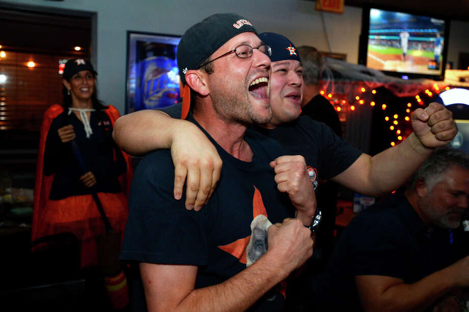 Cory Hidalga, left, and Pablo Ortiz cheer after an Astros home run while watching the World Series at The West Bar and Grill on Tuesday night.  Photo taken Tuesday 10/31/17 Ryan Pelham/The Enterprise Photo: Ryan Pelham / ©2017 The Beaumont Enterprise/Ryan Pelham