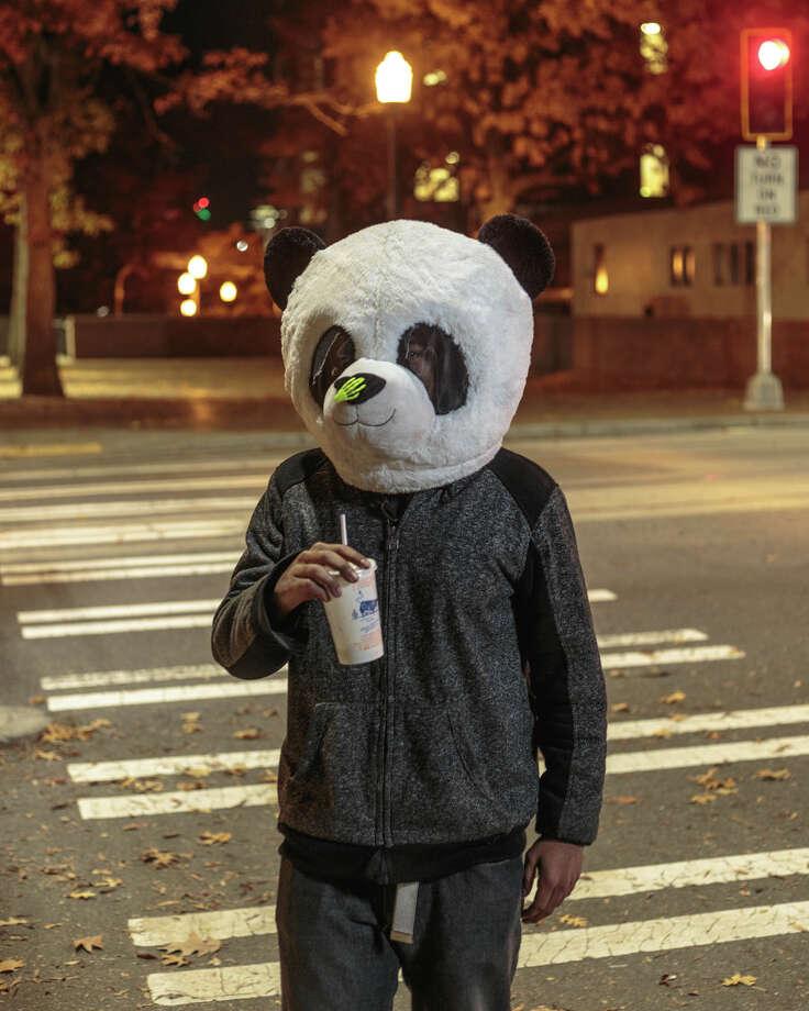 Zac Johnson wears a panda head on Halloween in Capitol Hill on Tuesday, Oct. 31, 2017. Photo: GRANT HINDSLEY, SEATTLEPI.COM / SEATTLEPI.COM